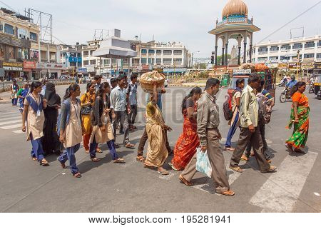 MYSORE, INDIA - FEB 20, 2017: Indian men and women walking on street with pedestrians on square with crossroad on February 20, 2017. Population of Karnataka is 62000000 people