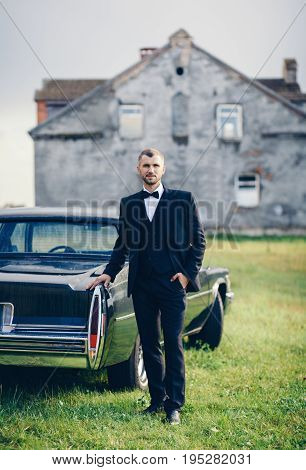 Handsome groom at wedding tuxedo smiling and waiting for bride near retro car. Elegant groom in black costume and bow-tie