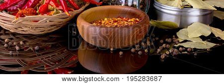 Spices and herbs, bay leaf, red chili peppers and wooden bowl of chili flakes on black banner background with reflection