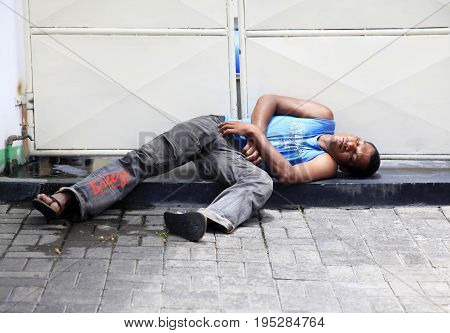 Pereber Mauritius - January 23 2012 : A homeless man sleeps on the sidewalk in city Pereber on Mauritius