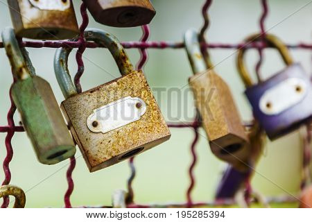 Close-up shot of old vintage rusty key locks on an old metal fence with blur background.