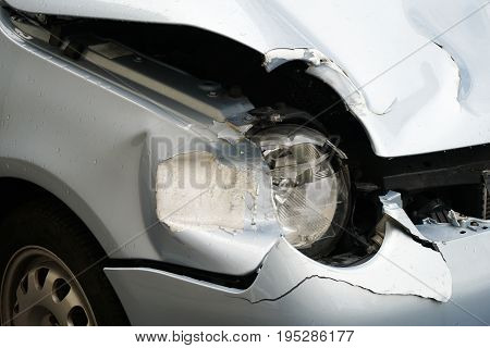 detail of car wreck after fender bender accident. broken headlight and battered hood.