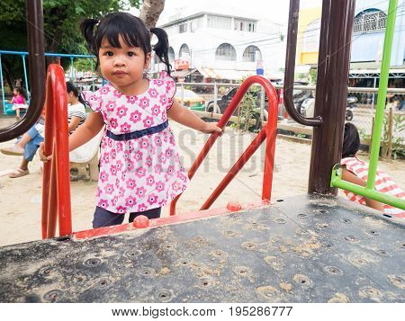 Asian girl playing slider after play sand on the playground.