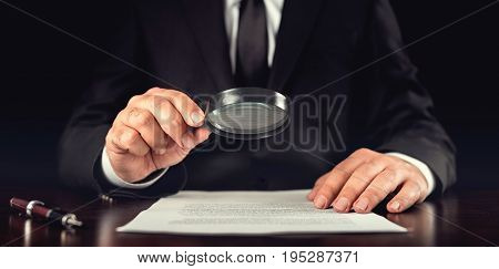 Businessman Reading Contract Details Before Signing In His Dark Office