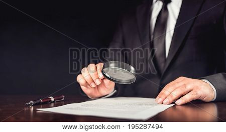 Businessman Reading Contract Details Before Signing In His Office