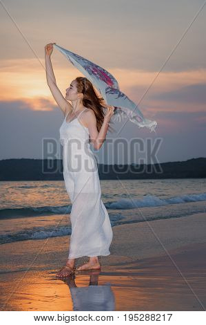 Beautiful women relax on the beachHappy young woman on the beach at the sun shining beach in ThailandYoung Lady in Relaxation on Tropical Beach with sandpetty girl walking in the sea at sunset