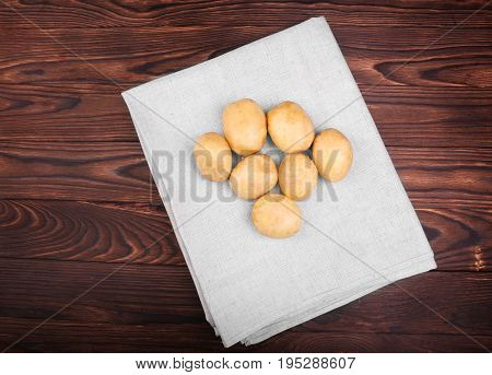 Harvest potatoes in a gray burlap sack on the dark wooden background. Delicious and fresh vegetables. Organic and uncooked new light brown potatoes. Fresh vegetables.