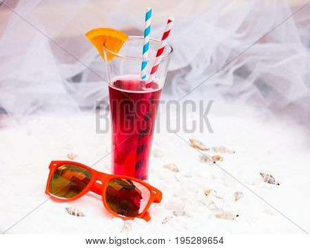 close up of red cool refreshing summer drink with straw in long glass and sunglasses on white sand with seashells background