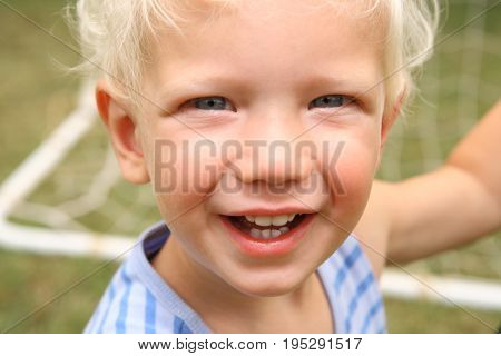 Cute Blonde little boy 4 year old kid face smiling and happy close up in front of soccer net, love, childhood
