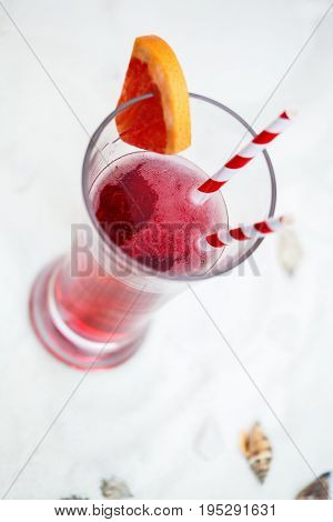 close up of red cool refreshing summer drink with straw in long glass on white sand with seashells background above view