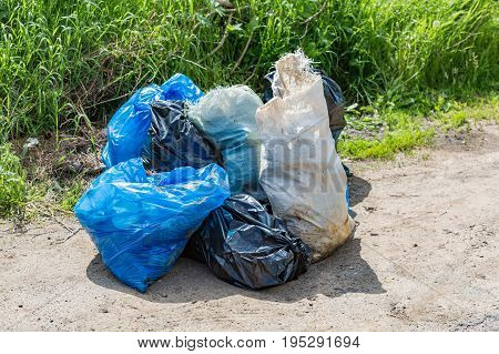 Blue white and black polyethylene bags with garbage lie on a dirt road