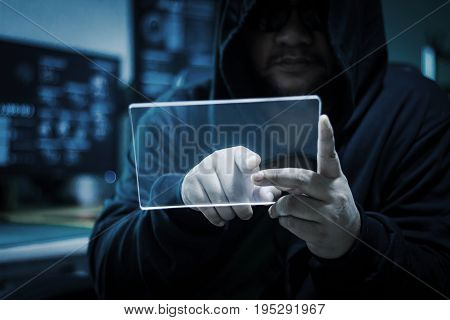 Hacker using blank clear glass tablet with blue dark and grain process concept for cyber technology data and network hacking criminal