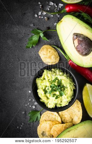 Traditional latinamerican mexican sauce guacamole chips and ingredients on black slate background. Top view.