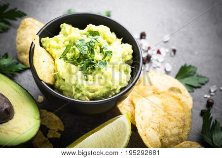 Traditional latinamerican mexican sauce guacamole chips and ingredients on black slate table.