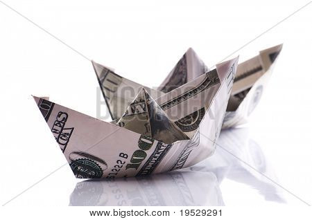 paper boats from dollars banknote on white