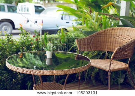 glass table and rattan wicker seat chair decoration outside the garden