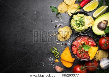 Latinamerican mexican food party sauce guacamole, salsa, chips and ingredients on black table. Top view copy space.