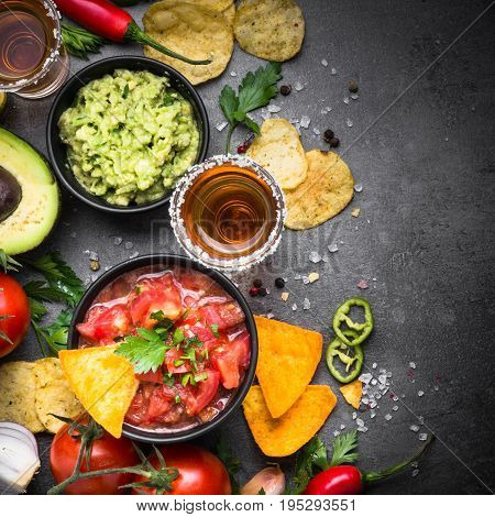 Latinamerican mexican food party sauce guacamole, salsa, chips and tequila on black table. Square.
