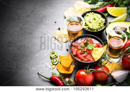 Latinamerican mexican food party sauce guacamole, salsa, chips and tequila on black table.