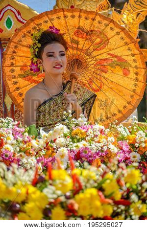 CHIANGMAI THAILAND - JANUARY 25 2015: Indigenous women and man with traitional costume sitting on decorated vehicle with flowers and bamboo hat fake elephants and chicken in parade of 22nd Traditional Skirt Fabric and The Indigenous Product and Culture Fe