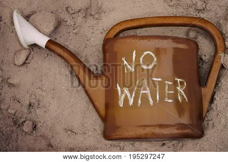 Empty water can with hand written text No Water laid on the sand