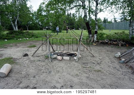 MACKINAW CITY, MICHIGAN / UNITED STATES - JUNE 18, 2017: A representation of an Anishnaabek barbecue pit stands in the Colonial Michilimackinac State Park.