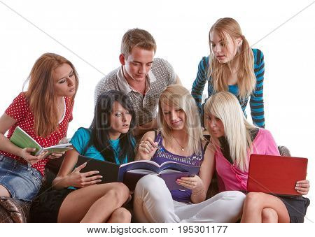 The group of young people sits on a sofa  with books and laptop  on a white background.