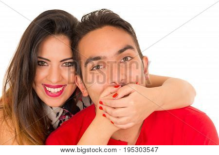 Close up of happy couple isolated on white background. Attractive man and woman being playful, woman putting her hands over his boyfriend mouth.