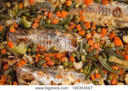 Baked fish with vegetables close-up. Mexican mixture and baked fish.
