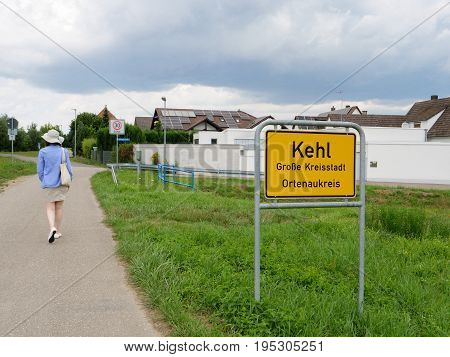 Unrecognizable woman walking near entrance to Kehl Germany yellow road sign with typical German architecture real estate buildings in the bakground and inscription Kehl Grosse kreisstadt Ortenaukreis