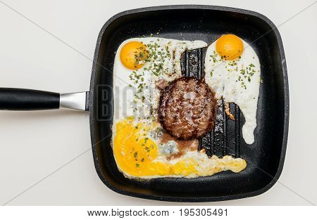 Overhead view above of delicious raw beef meat burger in a frying pan on cooking surface in kitchen with three fried eggs and one broken yolk