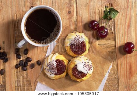 Cup of hot coffee and cookies with jam and sugar icing on old wooden table top view