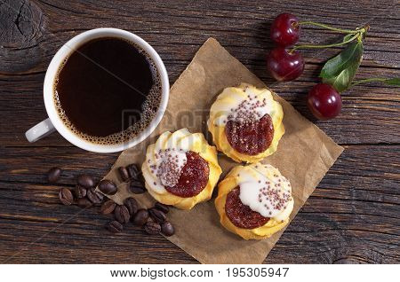 Cup of hot coffee and cookies with jam and sugar icing on dark wooden table top view