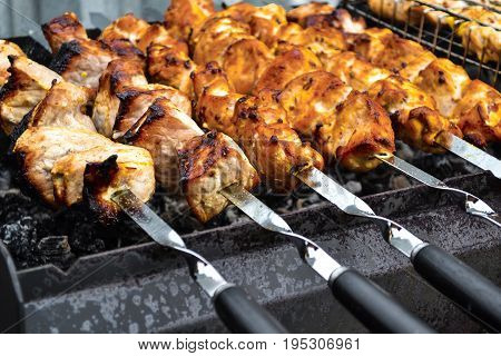 Grilled kebab cooking on metal skewer closeup. Roasted meat cooked at barbecue. Traditional eastern dish shish kebab. Grill on charcoal and flame picnic