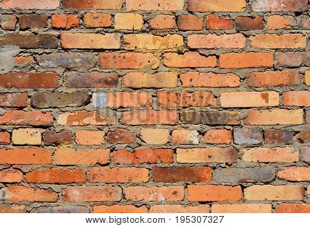 Brick wall of red uneven bricks. Brick wall