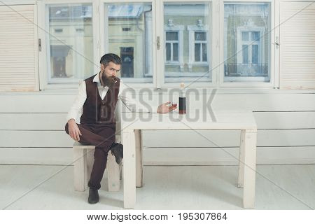 Hipster With Glass And Bottle Of Wine On Table
