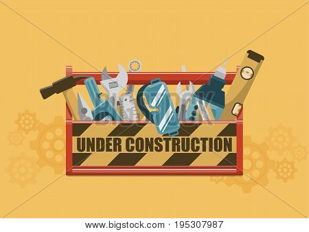 Under construction sign on red toolbox with tools on yellow gear wheels background
