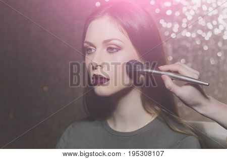fashion. girl or cute woman adorable fashionable model with long hair getting powder on face skin with makeup brush by female visagiste on glowing background. Visage make up. spa and skincare