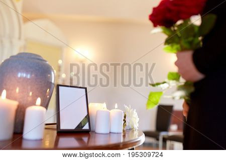 cremation, people and mourning concept -  cinerary urn, photo frame with black ribbon and woman holding red roses at funeral in church