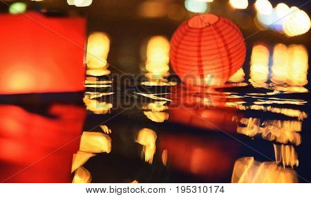 Paper lanterns floating in water at night lights