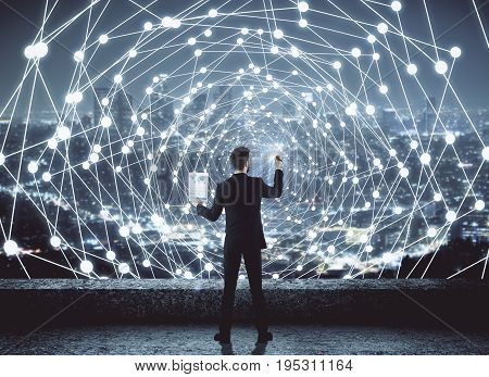 back view of young businessman drawing abstract polygonal digital mesh on night city background. Network and communication concept. 3D Rendering