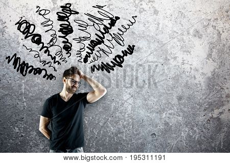 Pensive young man on concrete background with scribble. Confused concept