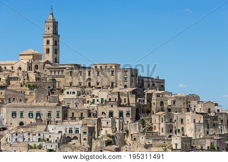 Old houses and a church in ancient architecture in the same kind of stone in a town built upon a hill known as the Sassi di Matera in Basilicata Italy.