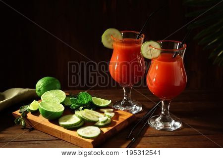 Delicious cocktails with tequila in glasses on table against dark background