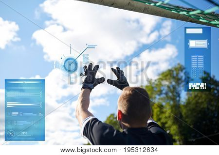 sport, technology and people concept - soccer player or goalkeeper catching ball at football goal on football field