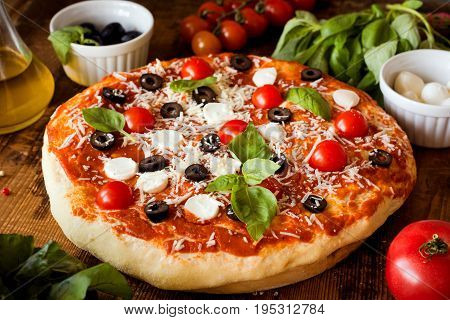 Pizza with tomatoes, mozzarella cheese, black olives and basil. Delicious italian pizza on wooden pizza board. Closeup view, selective focus