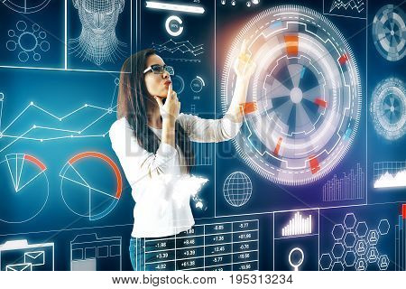 Thoughtful young european woman pressing digital button of large business hologram. Blue background. Information concept. 3D Rendering
