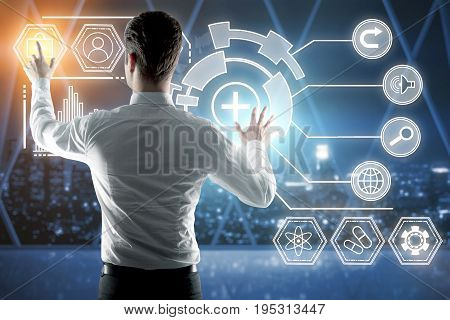 Back view of young businessman managing digital business charts in night office interior with city view. Technology future and accounting concept. 3D Rendering