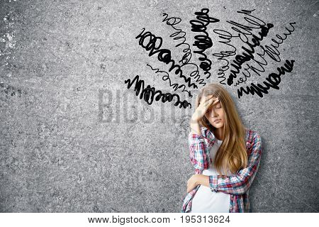 Pensive young woman on concrete background with scribble. Confusion concept