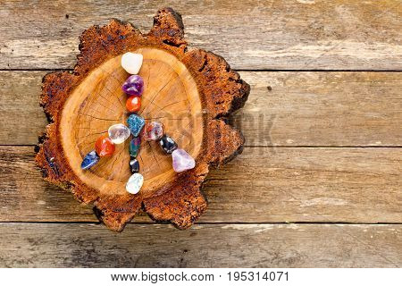 Peace Symbol In Crystals On Circle Of Timber Log Against Old Textured Wooden Background